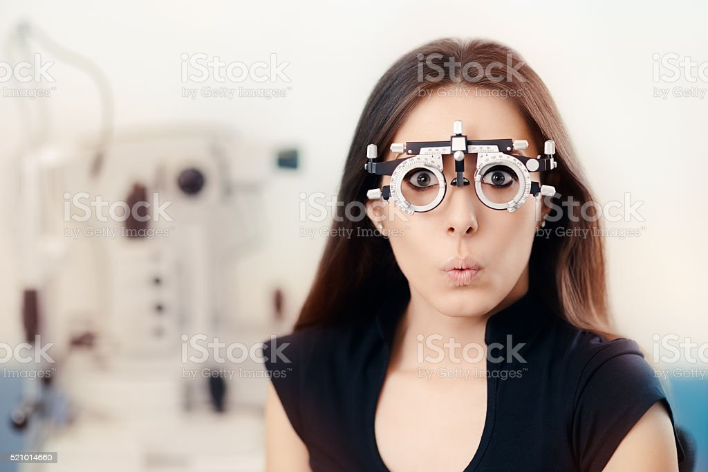Funny Girl at Ophthalmological Exam Wearing Eye Test Glasses stock photo