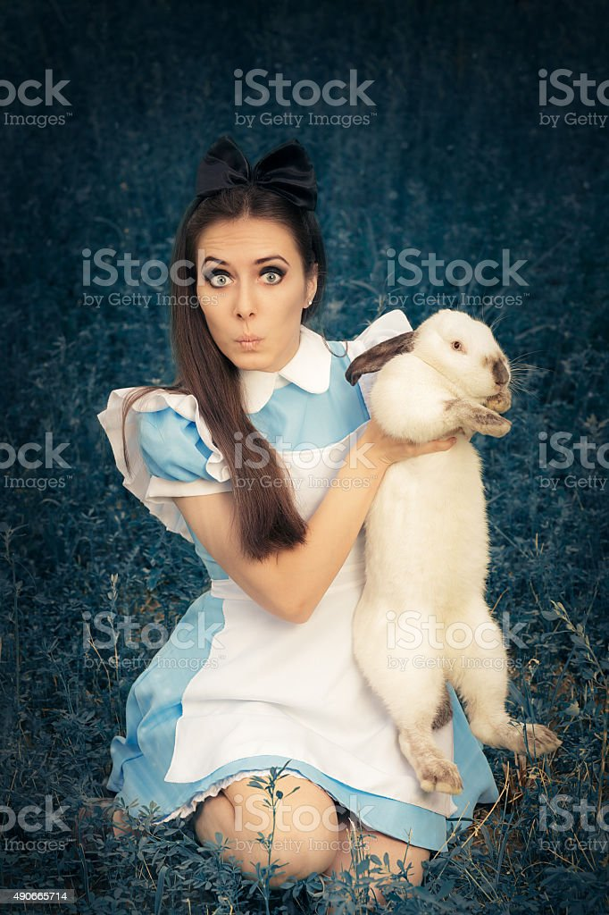 Funny Girl Costumed as Alice in Wonderland with her Rabbit stock photo