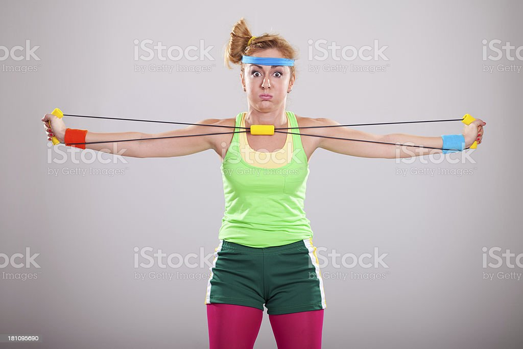 Funny girl doing tough exercises with resistance band royalty-free stock photo