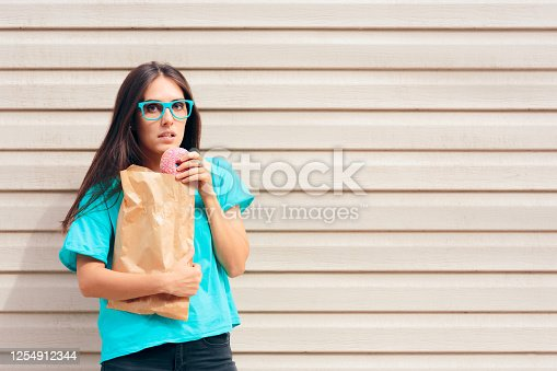 istock Funny Girl Eating Donuts Strait Out of a Paper Bag 1254912344