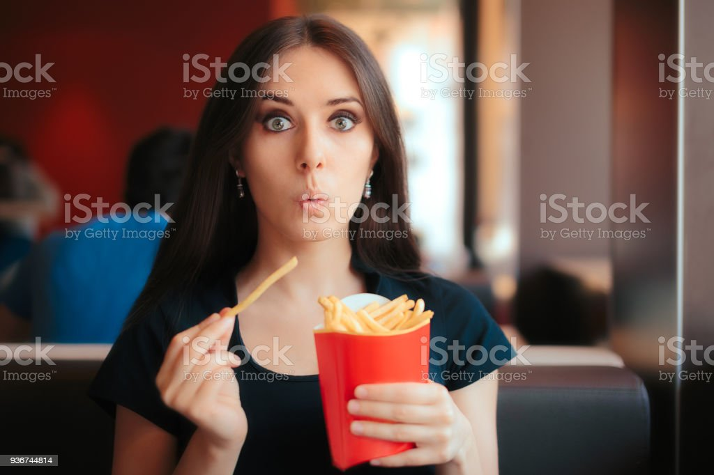 Funny Girl Eating Fries in French Fast Food Restaurant stock photo
