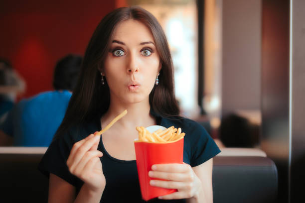 funny girl eating fries in french fast food restaurant - crisp packet stock photos and pictures