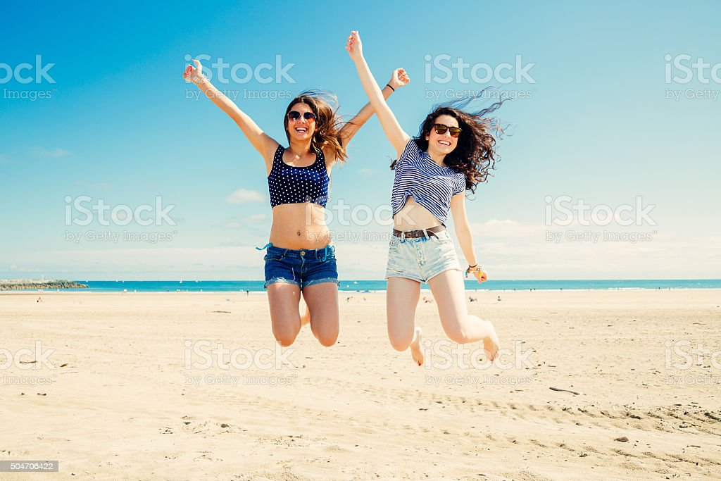 Funny girl frinds jumping on the beach stock photo