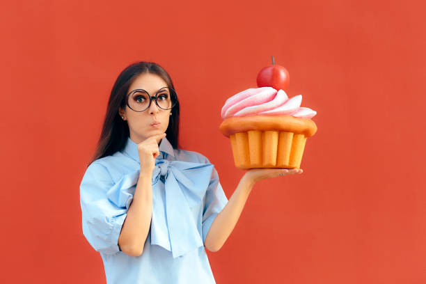 funny girl holding big huge giant sweet muffin cupcake - big cake stock photos and pictures
