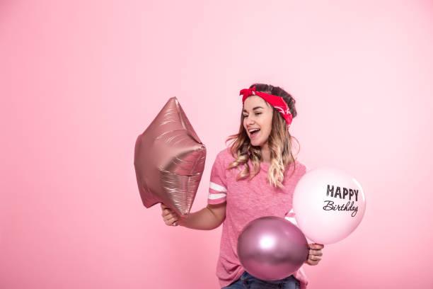 lustiges mädchen in einem rosa t-shirt mit luftballons happy birthday gibt ein lächeln und emotionen auf einem rosa hintergrund - pailletten shirt stock-fotos und bilder