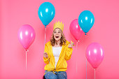 istock Funny girl in birthday hat, balloons and blowout horn on pastel pink background. Attractive trendy teenager celebrating birthday. 941906606