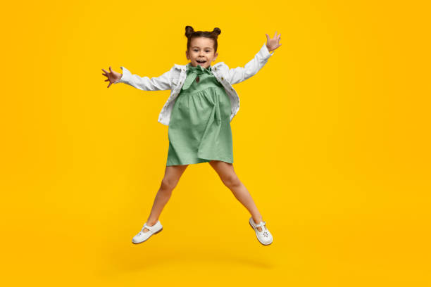 Funny girl in dress leaping up stock photo