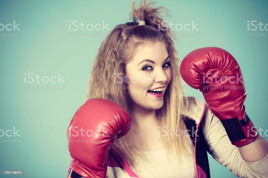 Funny blonde girl female boxer in big fun red gloves playing sports...
