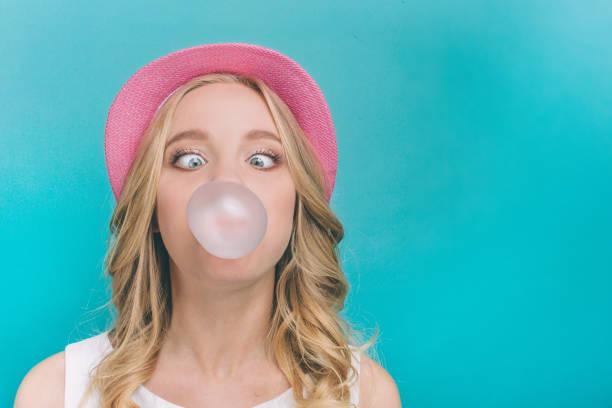 funny meisje is het opblazen van de bal van kauwgom. ook is ze op zoek op deze bal in een grappige positie. geïsoleerd op blauwe achtergrond. - kauwgom stockfoto's en -beelden