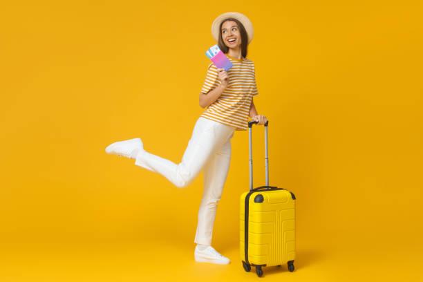 saut de fille drôle, tenant la valise et le passeport avec des billets d'avion, isolés sur le fond jaune - valise humour photos et images de collection