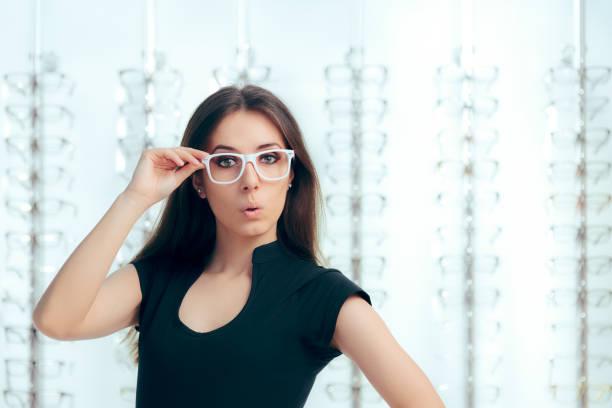 funny girl auf der suche nach neuen brillen im optischen speicher - lieblingsrezepte stock-fotos und bilder