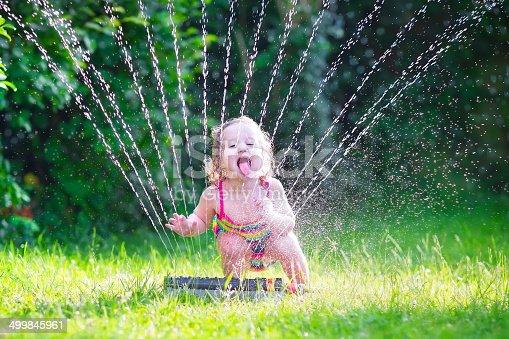 istock Funny girl playing with garden sprinkler 499845961