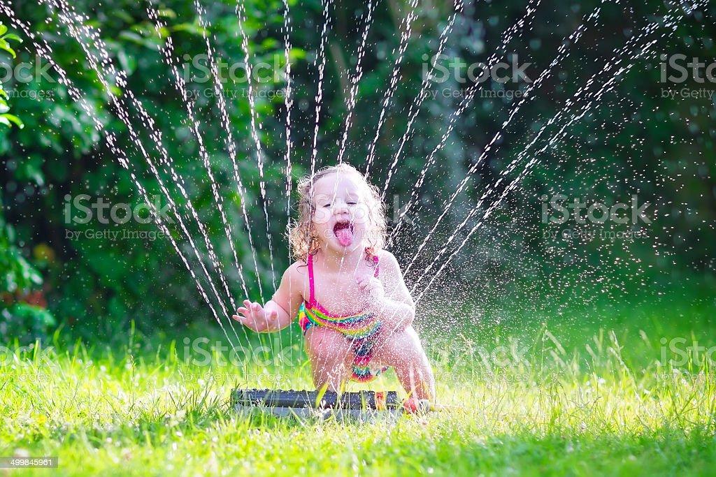 Engraçado garota brincando com jardim de sprinkler - foto de acervo