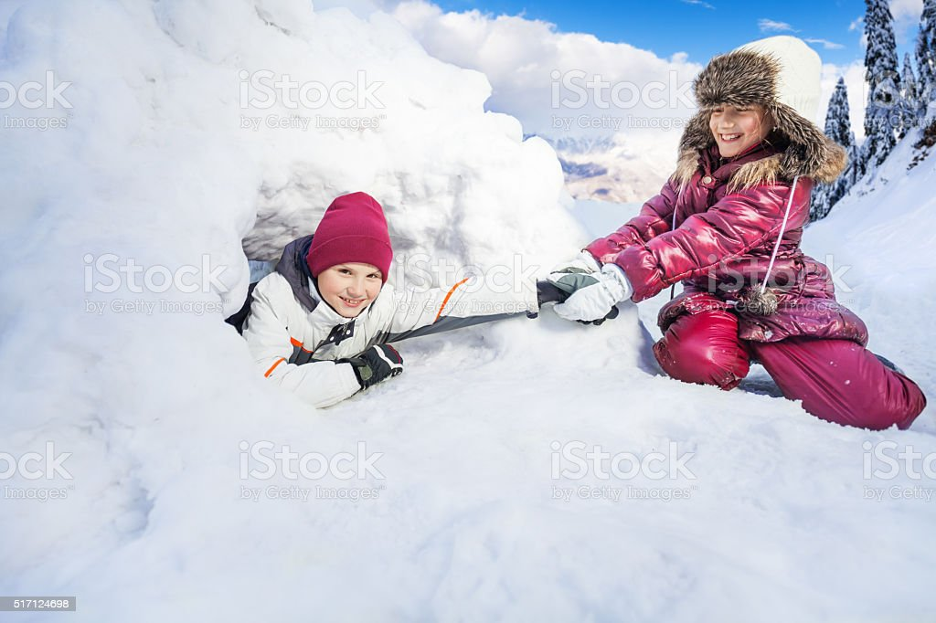 Funny girl pull on her friend from the snow igloo stock photo