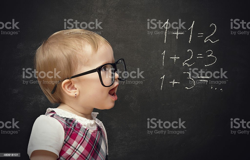 funny girl pupil solves arithmetic examples on blackboard royalty-free stock photo