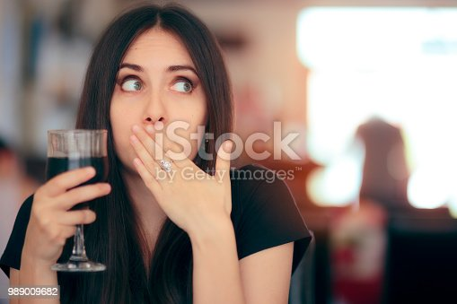 Woman covering her moth after drinking cola