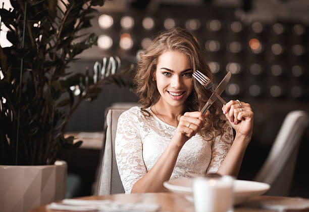 Funny girl sitting in restaurant stock photo