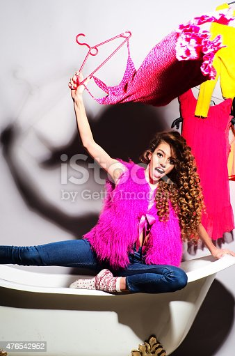 istock Funny girl sitting on bathtub with clothes 476542952