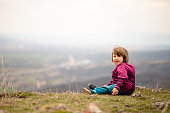 Cheerful little girl sitting on the grass and enjoying fresh day at mountain