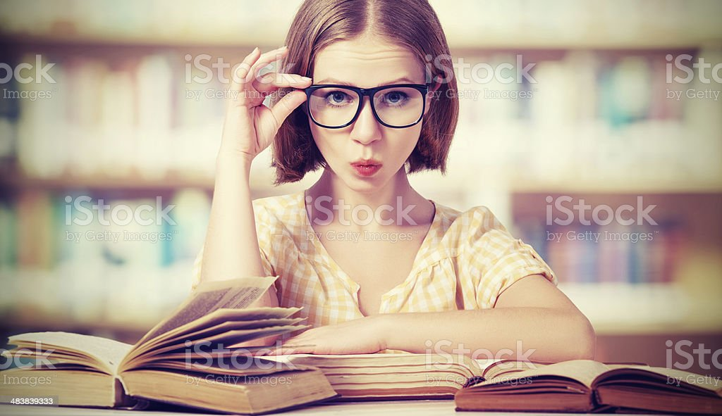 funny girl student with glasses reading books royalty-free stock photo