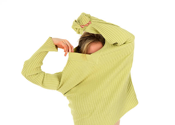 Funny girl takes off a green sweater Funny girl takes off a green stylish sweater. undressing stock pictures, royalty-free photos & images