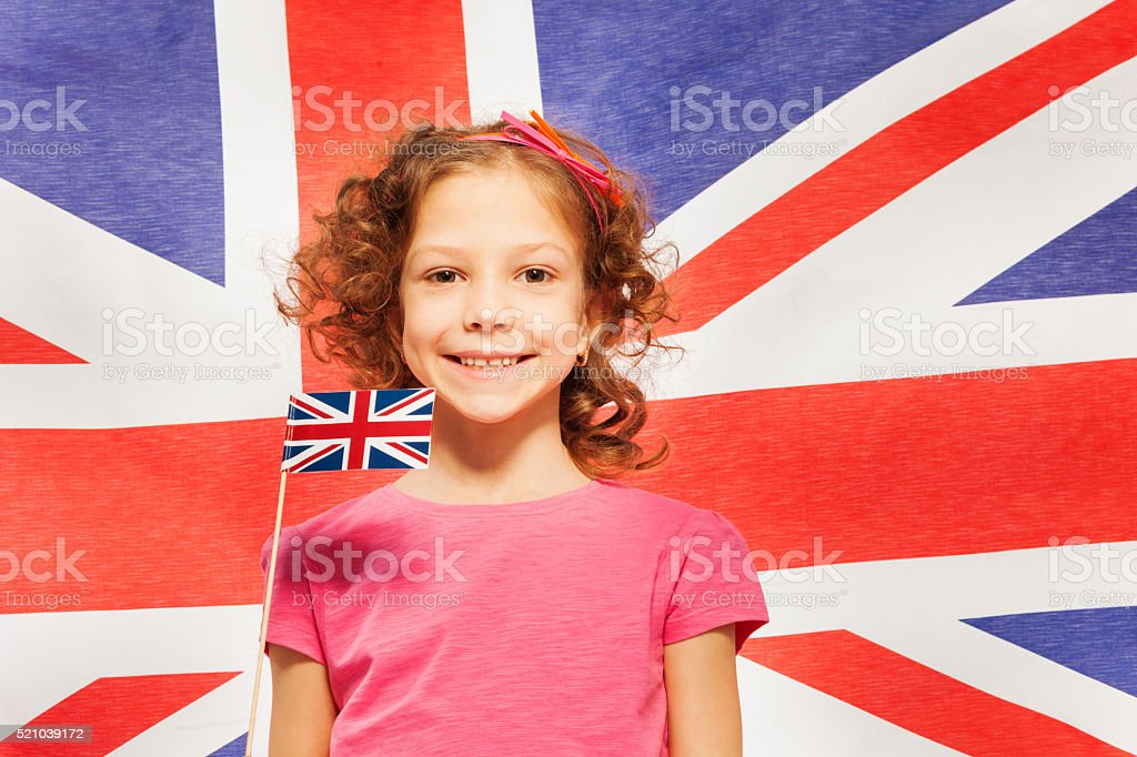 Funny girl with little flag against British banner stock photo