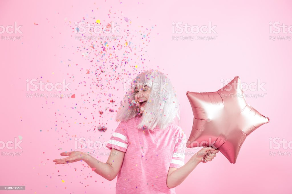 Funny Girl with silver hair gives a smile and emotion on pink background. Young woman or teen girl with balloons and confetti стоковое фото