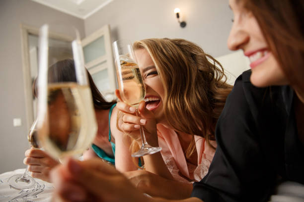 Funny girls drinking a champagne while lying on the bed, celebrating event stock photo