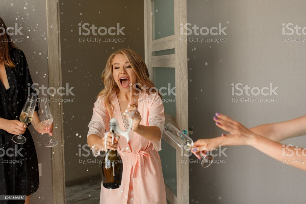 Funny girls making toast with champagne glasses at the hen-party stock photo