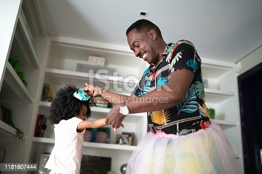 Funny grandfather with tutu skirts dancing like ballerinas with grand daughter