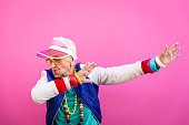 Funny grandmother portraits. 80s style outfit. trapstar taking a selfie on colored backgrounds. Concept about seniority and old people