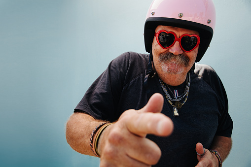 Silly senior adult man with pink safety helmet and red heart shape sunglasses, isolated on blue wall background