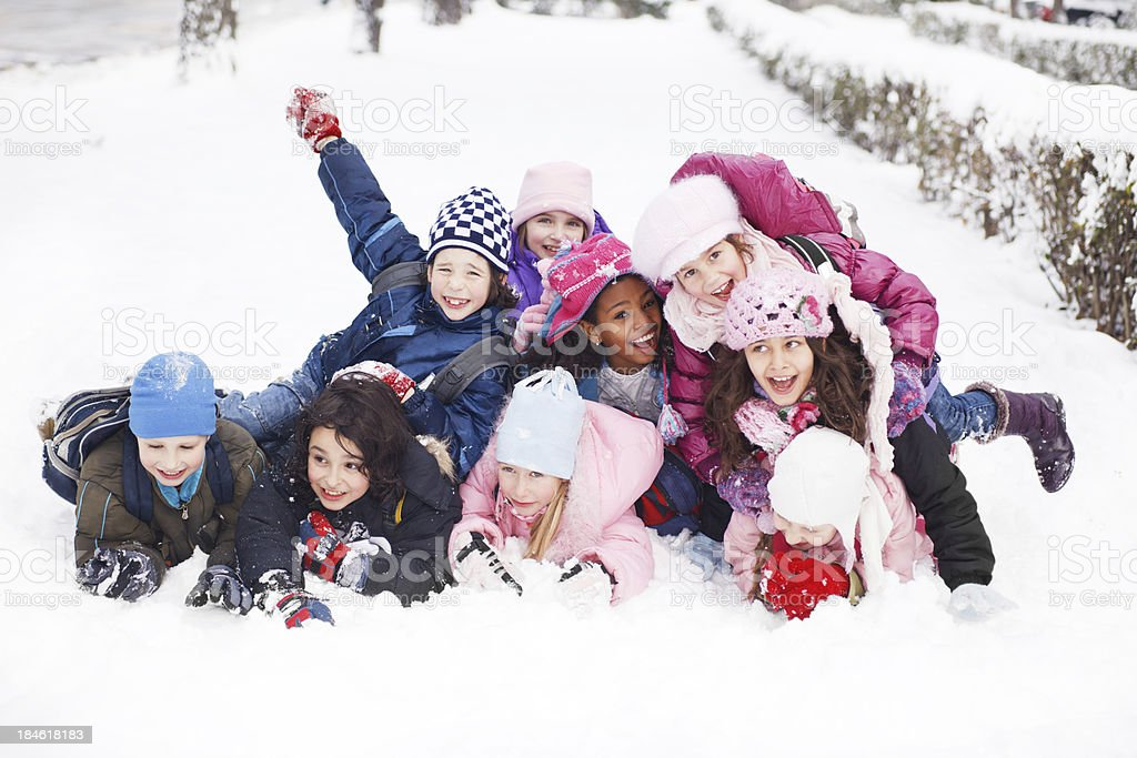 Funny group of children are lying in the snow. stock photo