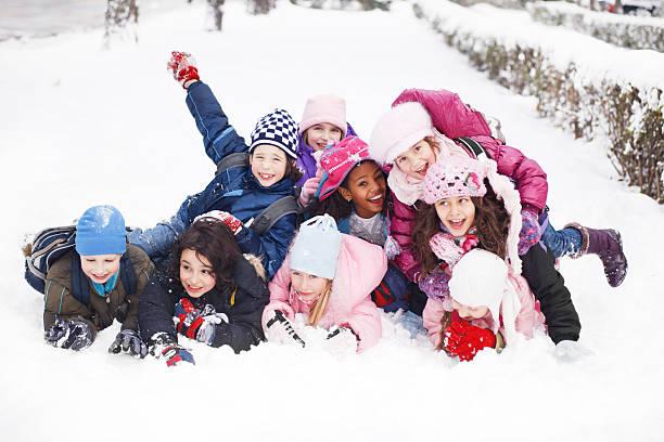 lustiger gruppe von kindern im schnee liegen. - schneespiele stock-fotos und bilder