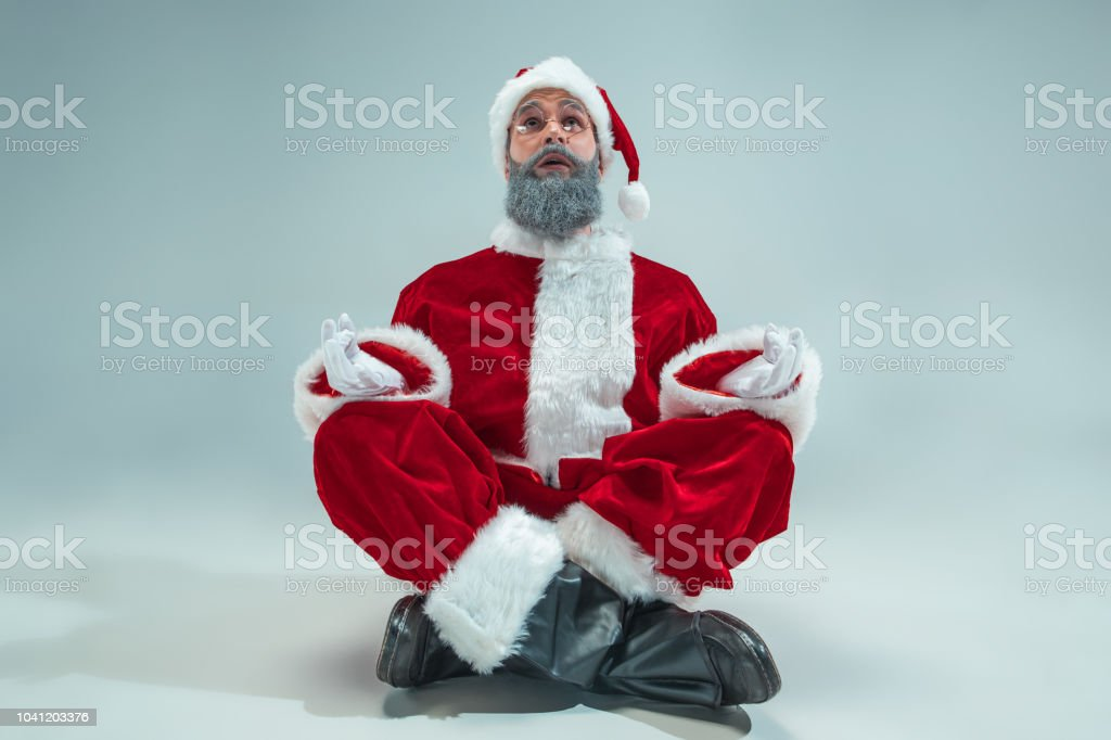 Funny serious guy with christmas hat sitting at yoga pose at studio....