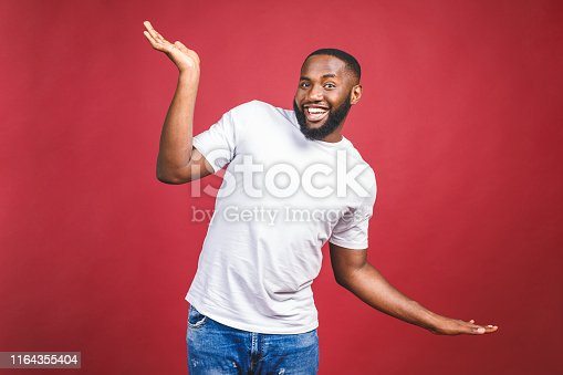 925466128istockphoto Funny guy in white t-shirt jumping and looking at camera. Studio portrait of emotional african male model posing on red background. 1164355404