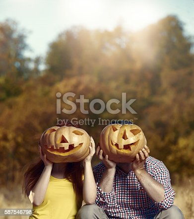 lifestyle shot of man and woman covering their faces with Jack o'lanterns, enjoying Halloween in autumn day.