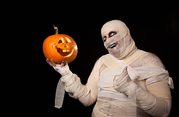 Funny halloween mummy with smiling pumpkin Funny halloween mummy with smiling pumpkin holding thubs up costume stock pictures, royalty-free photos & images