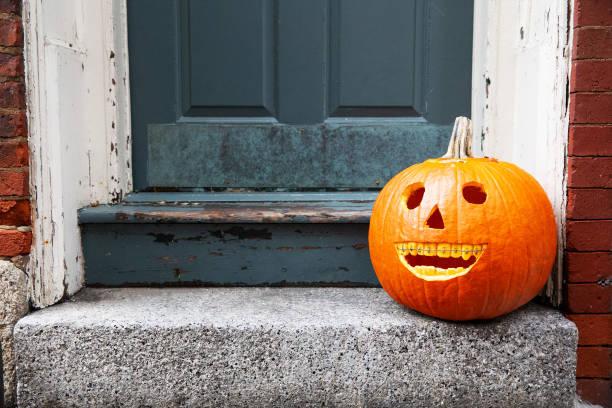 lustige Halloween-Kürbis vor der Haustür. lächelnder Kürbis mit Hosenträgern. das Konzept der Zahnarztpraxis. – Foto