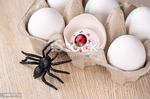 istock Funny halloween treats, eyeball in egg on wooden background, copy space, closeup 1049310724