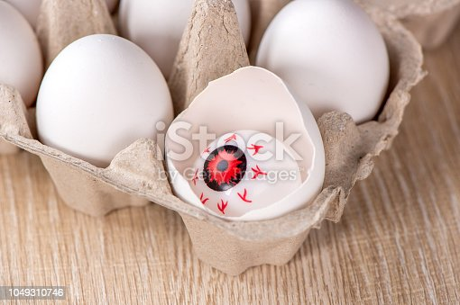 istock Funny halloween treats, eyeball in egg on wooden background, copy space, closeup 1049310746