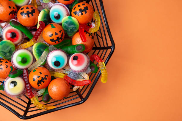funny haloween candy in a spiderweb bowl - halloween candy стоковые фото и изображения