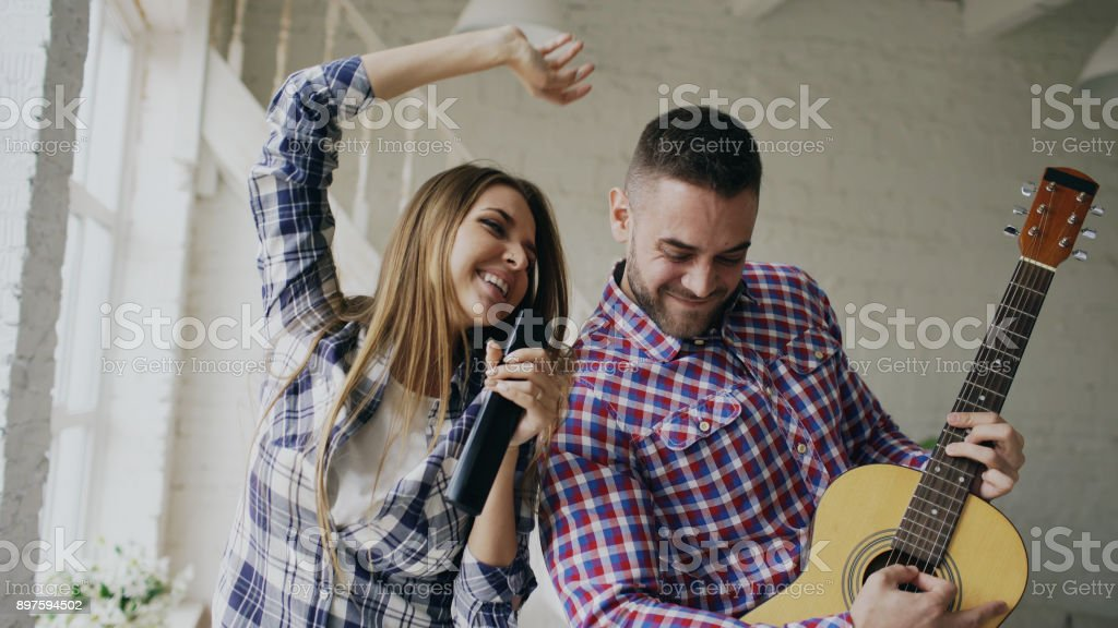 Funny happy and loving couple dancing and playing guitar. Man and woman have fun during their holiday at home stock photo