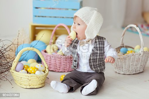 istock Funny happy baby boy in bunny hat, tie bow and suit playing with Easter eggs. Eating egg 924437084