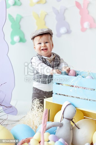 istock Funny happy baby boy in hat, tie bow and suit playing with Easter eggs. Rabbit banners on wall 924436906