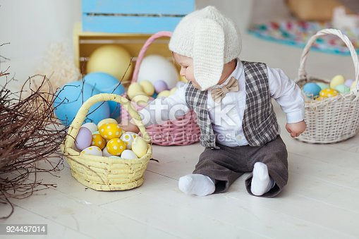 istock Funny happy baby boy in hat, tie bow and suit playing with Easter eggs. Rabbit banners on wall 924437014