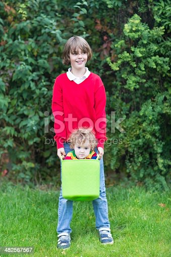 954356678istockphoto Funny happy brother and baby sister playing with laundry basket 482567567