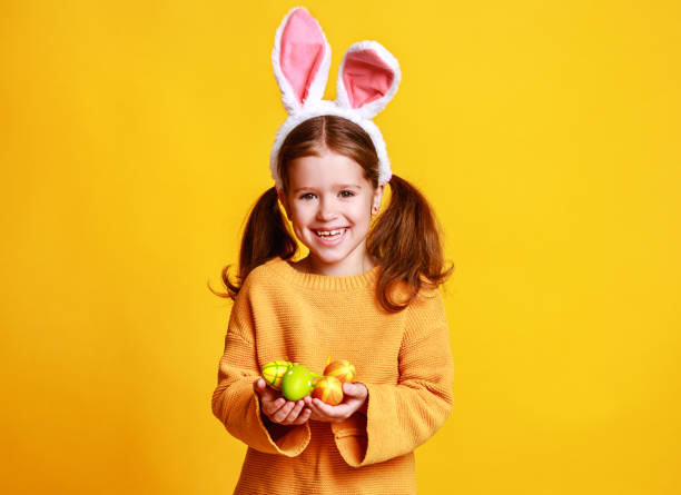 Funny happy child girl with easter eggs and bunny ears on yellow picture id1131827454?b=1&k=6&m=1131827454&s=612x612&w=0&h=f6njjm96klknxg0q5xuradfbse1o8hllr1wmdlvbz9s=