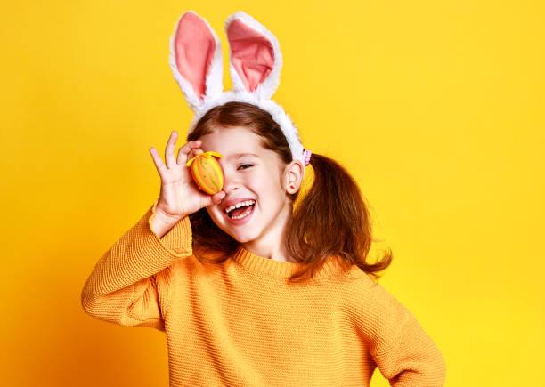 divertida niña feliz niño con huevos de pascua y orejas de conejo en amarillo - pascua fotografías e imágenes de stock