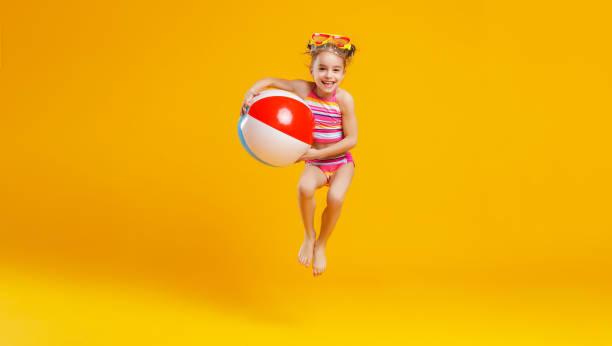 engraçado criança feliz pulando em traje de banho em fundo colorido - roupa de natação - fotografias e filmes do acervo